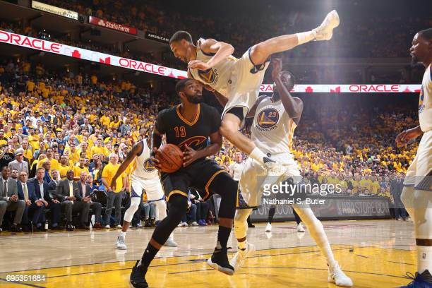 Tristan Thompson of the Cleveland Cavaliers drives to the basket while defended by Draymond Green and Klay Thompson of the Golden State Warriors in...