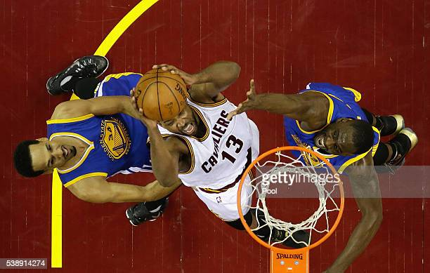 Tristan Thompson of the Cleveland Cavaliers drives to the basket against Draymond Green of the Golden State Warriors and Shaun Livingston during the...