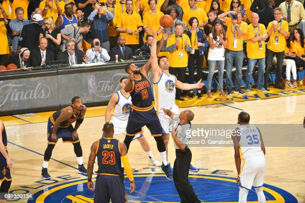Tristan Thompson of the Cleveland Cavaliers goes up for the opening tip off against Zaza Pachulia of the Golden State Warriors in Game One of the...