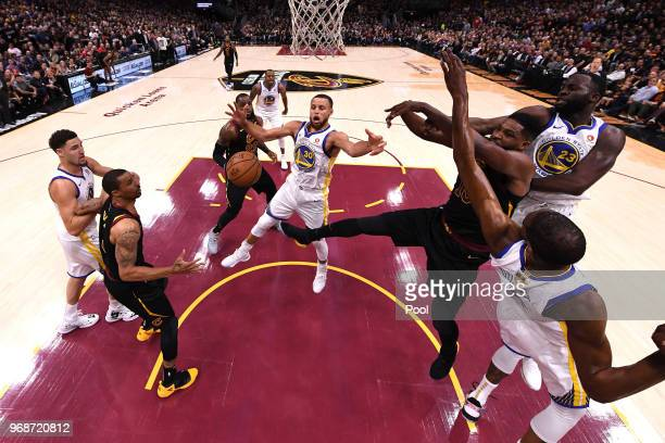 Tristan Thompson of the Cleveland Cavaliers throws a pass defended by Draymond Green Stephen Curry and Kevin Durant of the Golden State Warriors in...