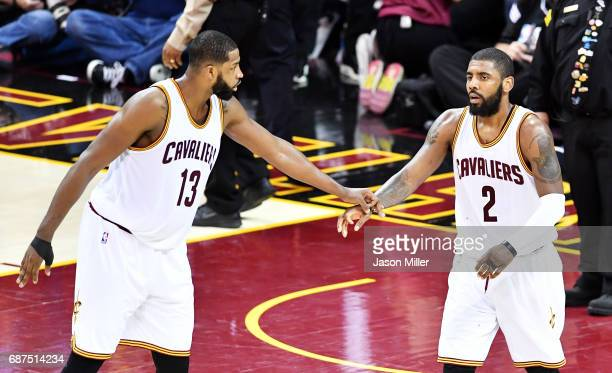 Tristan Thompson talks to Kyrie Irving of the Cleveland Cavaliers after Irving was injured in the second half against the Boston Celtics during Game...