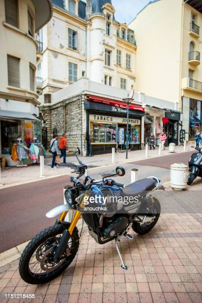 triumph motorcycle parked in biarritz city center, france - triumph motorcycle stock pictures, royalty-free photos & images