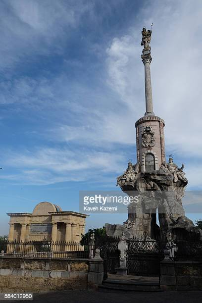 Triumph of Saint Raphael l column with the Bridge Gate monument seen in the background on June 26 2016 in Cordoba Spain The column is a symbol of...