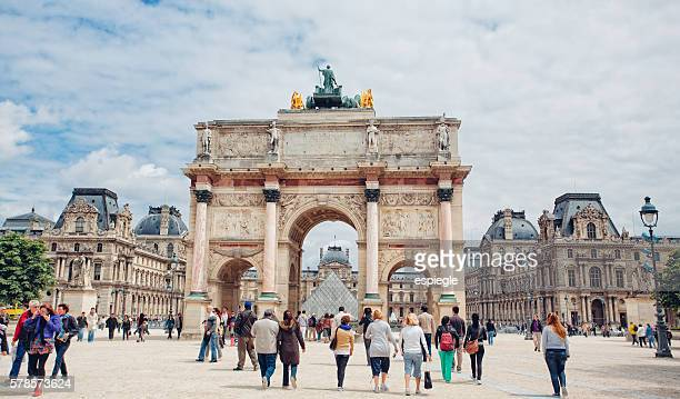 triumphal arch and louvre palace in paris, france - musee du louvre stock photos and pictures
