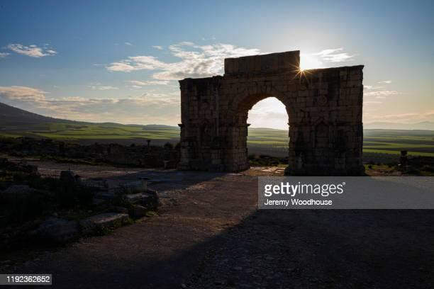 triumphal arch at the end of the via appia at volubilis - volubilis fotografías e imágenes de stock