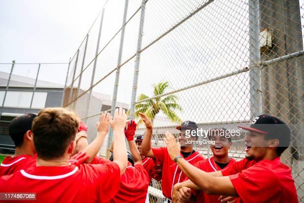 勝利のヒスパニックの野球選手はハイファイブで祝う - 高校野球 ストックフォトと画像