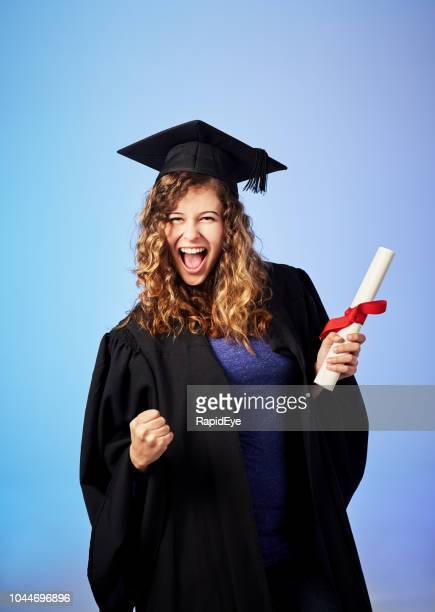 Triumphant young female graduate punching air and smiling