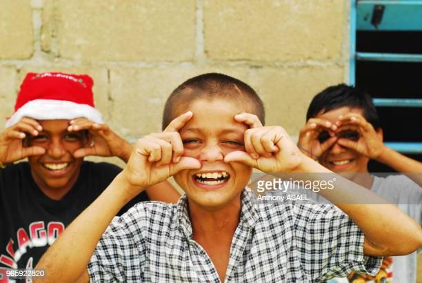 Trois enfants imitant le geste de photographier l'un d'eux porte un chapeau de Père Noel Belise