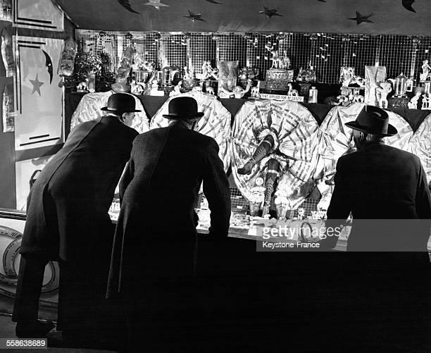 Trois hommes d'affaires jouant au stand de la 'Jarretière' à la fête foraine de Londres, Royaume-Uni, circa 1950.
