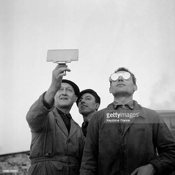 Trois hommes utilisant un verre fumé et des lunettes de soudeur pour regarder l'eclipse du soleil à Paris France le 15 février 1961