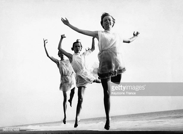 Trois jeunes filles en tuniques blanches sautent en l'air bras écartés sur une plage