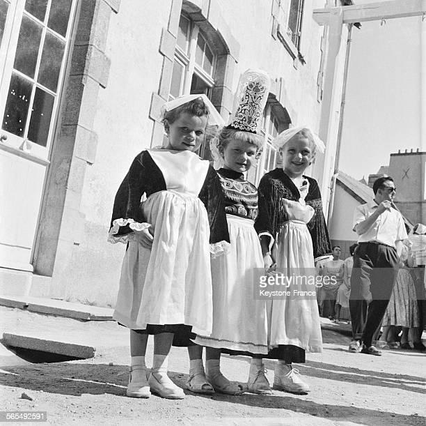 Trois petites filles portant un costume du folklore breton avec la coiffe et les chaussures blanches à Quiberon France en 1957