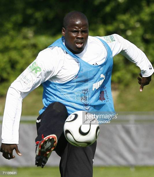 Ivorian defender Emmanuel Eboue controls a ball paste teammate Kolo Toure 06 June 2006 during a training session of the Elephants, the Ivorian...
