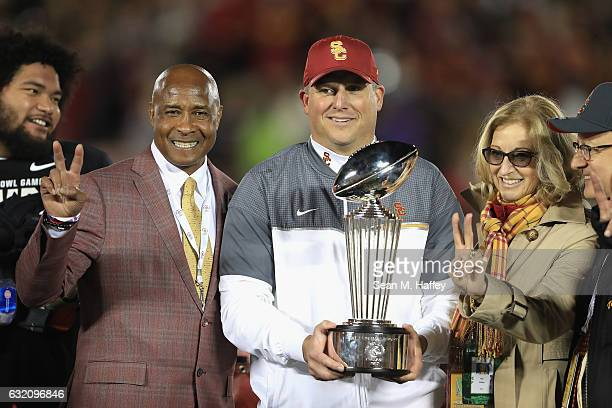 Trojans athletic director Lynn Swann and USC Trojans head coach Clay Helton pose with the 2017 Rose Bowl trophy after defeating the Penn State...