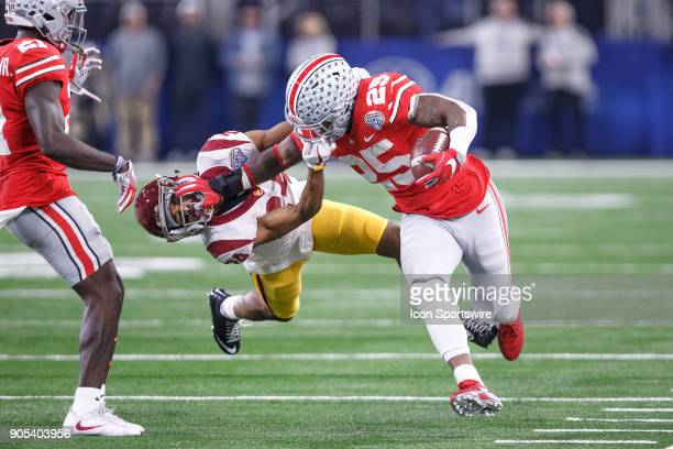 Trojans cornerback Isaiah Langley tries to pull Ohio State Buckeyes running back Mike Weber down by the facemask during the Cotton Bowl Classic...