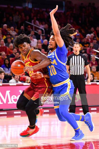 Trojans guard Ethan Anderson drives to the basket against UCLA Bruins guard Tyger Campbell during the college basketball game between the UCLA Bruins...