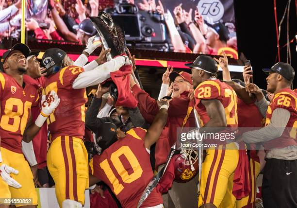 Trojans head coach Clay Helton and members of the team hoist the PAC12 trophy during the awards ceremony following the PAC12 Championship game...