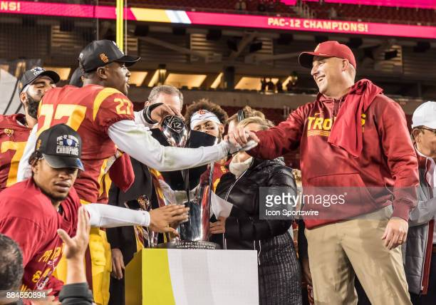 Trojans head coach Clay Helton congratulates USC Trojans cornerback Ajene Harris during the trophy ceremony after the PAC12 Championship game between...