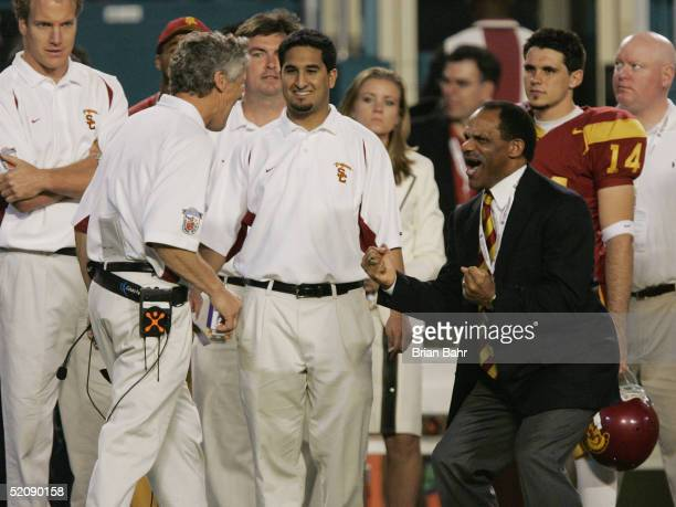 Trojans head coach Pete Carroll is congratulated by USC Athletic Director Mike Garrett during the closing minutes against the Oklahoma Sooners in the...