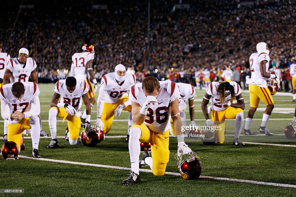 USC Trojans players kneel to pray in the end zone before the game against the Notre Dame Fighting Irish at Notre Dame Stadium on October 17, 2015 in South Bend, Indiana.