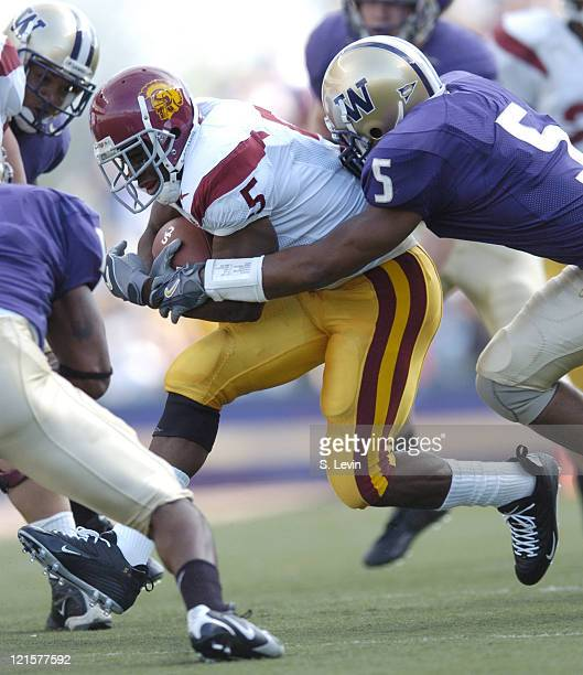 Trojans Reggie Bush tries to break free from Huskies Durrell Moss during the game between the USC Trojans and the University of Washington Huskies at...