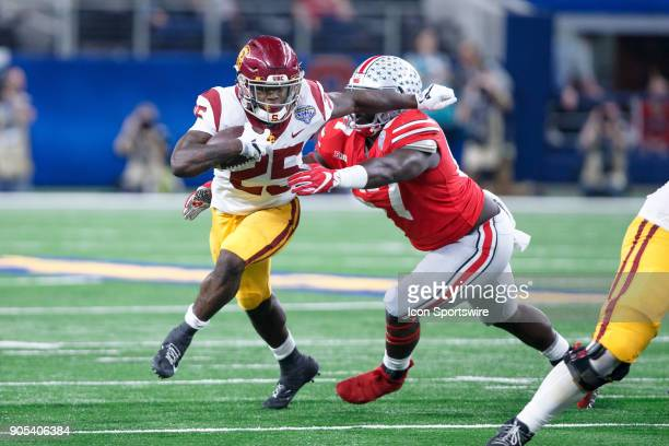 Trojans running back Ronald Jones II tries to break away from Ohio State Buckeyes defensive tackle Robert Landers during the Cotton Bowl Classic...