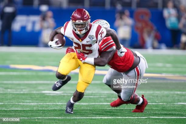 Trojans running back Ronald Jones II tries to break free of Ohio State Buckeyes defensive tackle Robert Landers during the Cotton Bowl Classic...