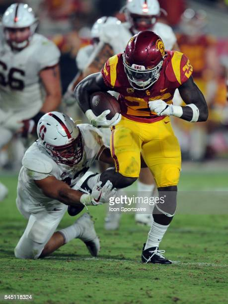 Trojans tailback Ronald Jones II gets tripped up by Stanford Cardinal line backer Mike Tyler during the fourth quarter of a game played on September...