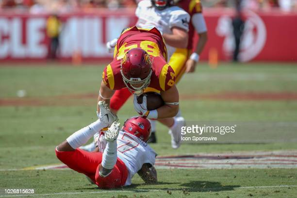 Trojans tight end Erik Krommenhoek catches the ball and gets tackled by UNLV Rebels defensive back Jericho Flowers during the college football game...