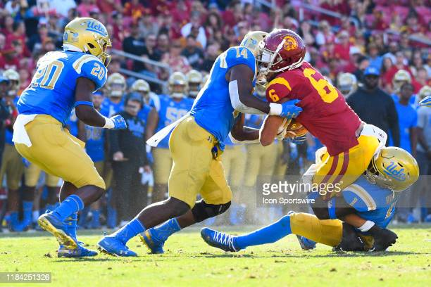 Trojans wide receiver Michael Pittman Jr is tackled by UCLA Bruins linebacker Krys Barnes and UCLA Bruins defensive back Darnay Holmes during a...