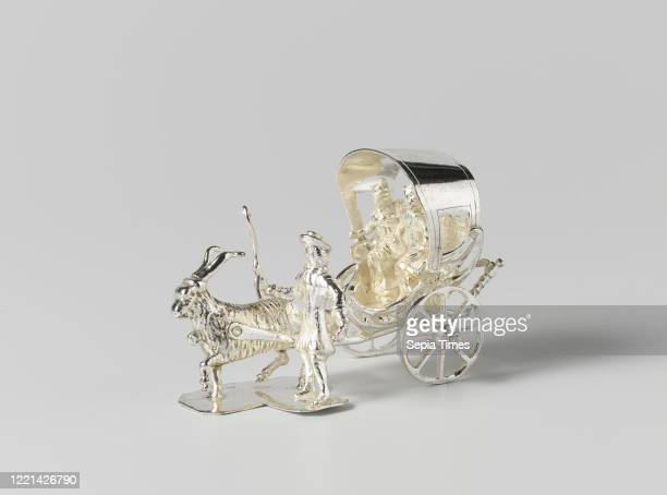 Trolley, Bokkewagen with hood, pulled by a goat. There is a man and a woman in the car. Next to the goat stands a man with a whip in his raised right...