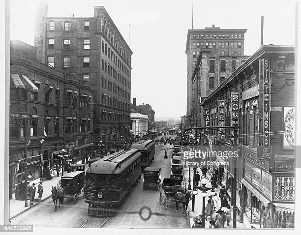 A trolley car shares Sixth Avenue with automobiles and horse drawn wagons in Des Moines Iowa in 1910
