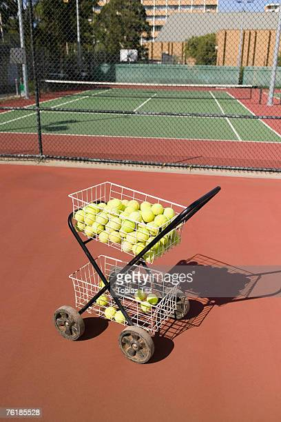 A trolley full of tennis balls at the edge of a tennis court