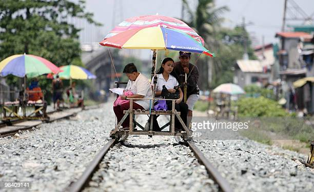 A trolley operator services passengers on a train track in Manila on June 26 2009 Up to five million people in the Philippines have likely been...