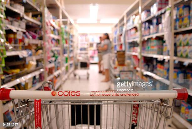 A trolley stands in an aisle with customers shopping at a Coles supermarket in Noosa Australia on Sunday Sept 16 2007 Coles Group Ltd the supermarket...