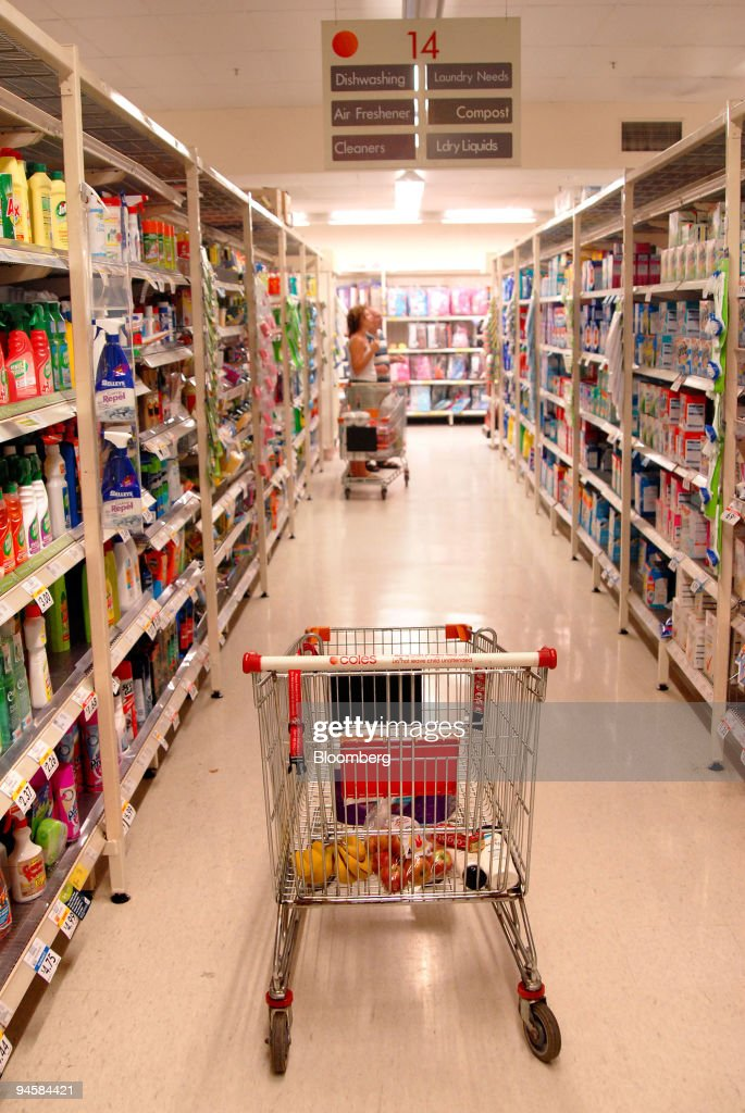 A trolley stands in an aisle with customers shopping at a Co : News Photo