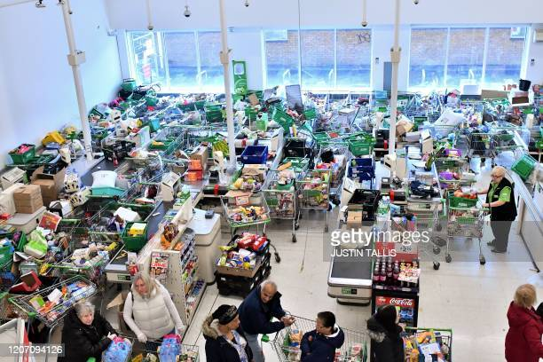 TOPSHOT Trolleys piled high for delivery are seen as shoppers queue at the checkout of a supermarket in London on March 14 as consumers worry about...