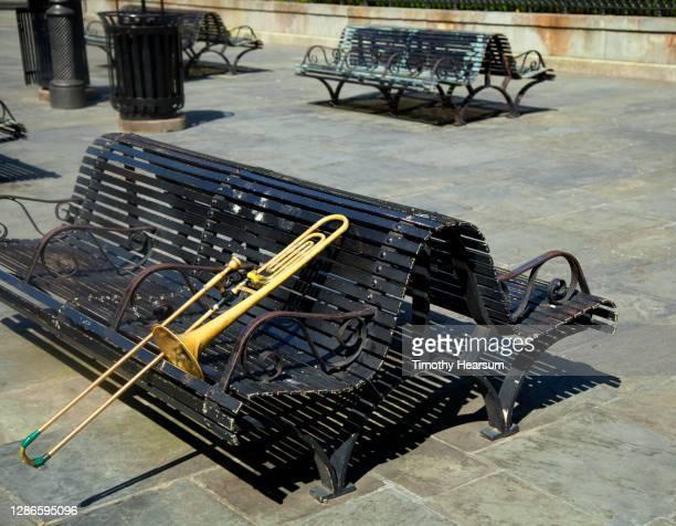 trombone leaning against a double park bench in jackson square - timothy hearsum photos et images de collection
