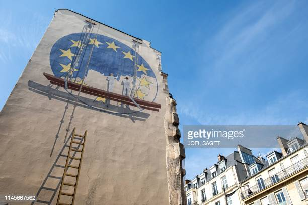 TOPSHOT A trompe l'oeil shows two workers painting the European Union flag on the side of a building in the French capital Paris on May 23 2019...