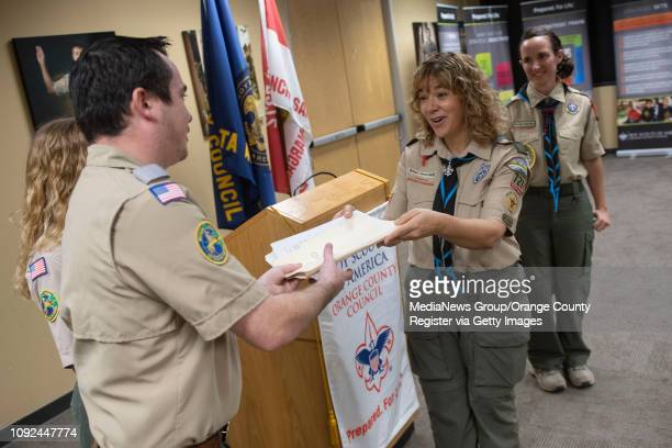Troop leader Monique Chrisope hands in the signed application documents for the county's first allgirl Boy Scout Troop to District Executive Anthony...