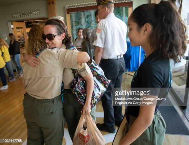 Troop leaders Monique Chrisope and Dea Del Rosario greet each other with a hug before a ceremony to submit an application for the county's first...