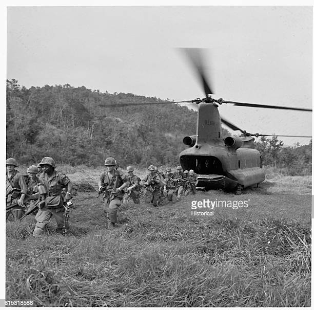 A troop of American soldiers head out from a CH47 helicopter after it lands Vietnam 1967