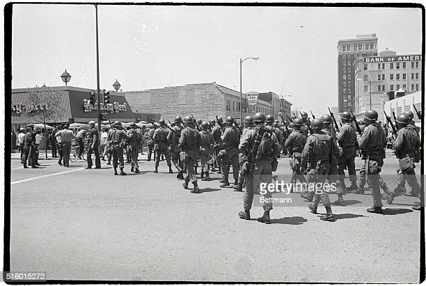 A troop of National Guardsmen stand near student protesters as they march to City Hall to protest a violent conflict between students and Guardsmen...