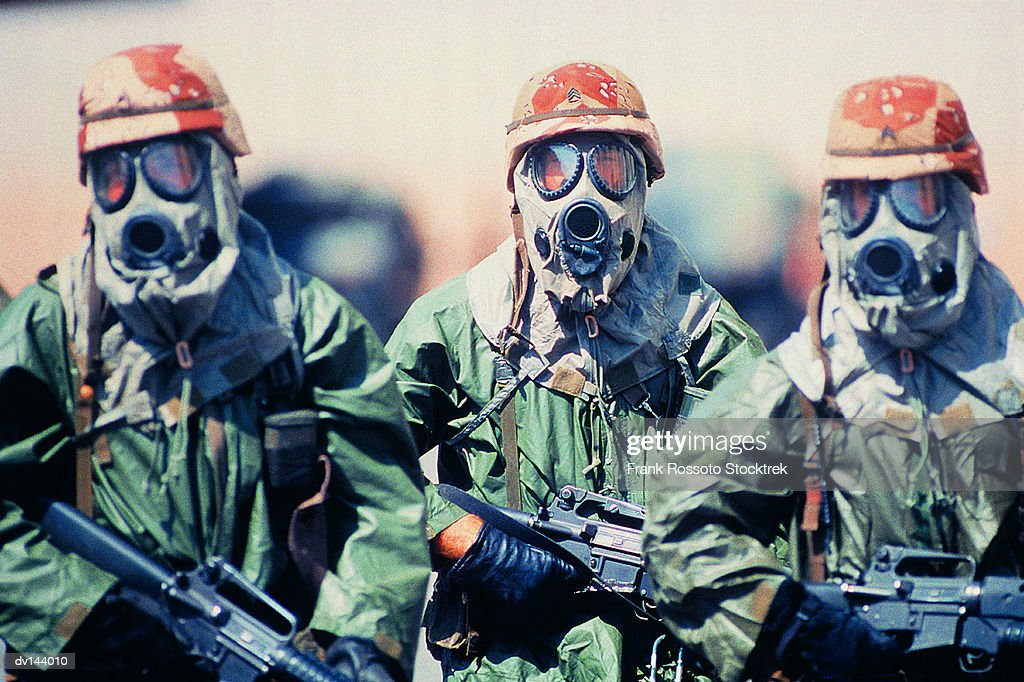 Troop of soldiers in camouflage uniforms, helmets and gas masks : Stock Photo