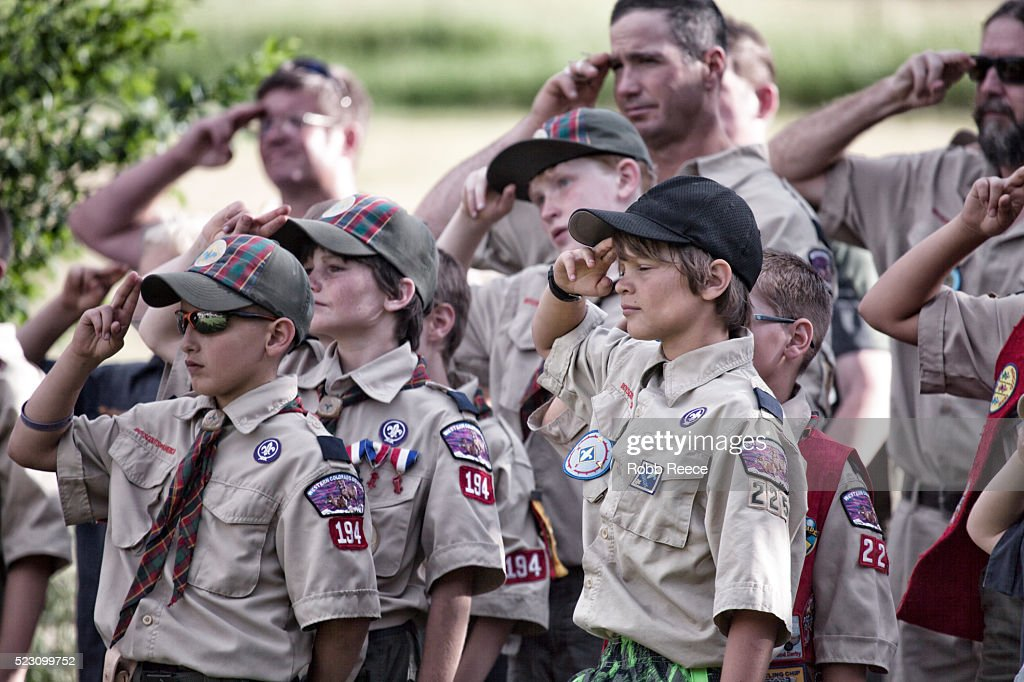 A troop of young, Weblo Boy Scouts salute during an America flag ceremony at their camp in Colorado. : Stock Photo