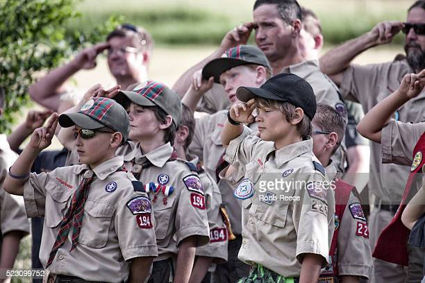a troop of young, weblo boy scouts salute during an america flag ceremony at their camp in colorado. - robb reece stock pictures, royalty-free photos & images
