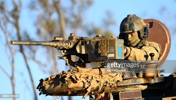 Trooper Luke Peterson from the 2nd Calvary Regiment holds onto a 50 cal machine gun on the top of his ASLAV during the 3rd Brigade Live Fire Exercise...