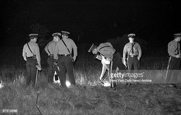 Troopers inspect Coston's body in high grass 50 yards off the Jersey Turnpike JoAnne who had been hiding in grass surrendered a short distance away...