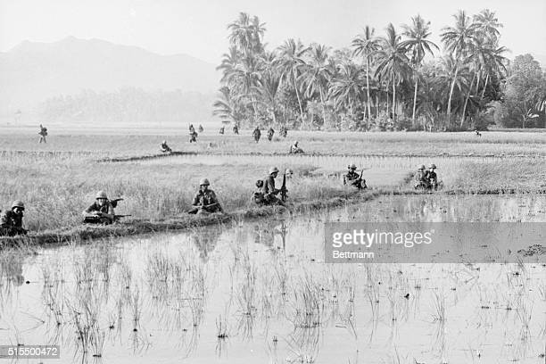 Troopers of the 1st Cavalry Division's Reconnaissance Unit scatter quickly to take up a defensive position in the middle of a rice paddy field near...
