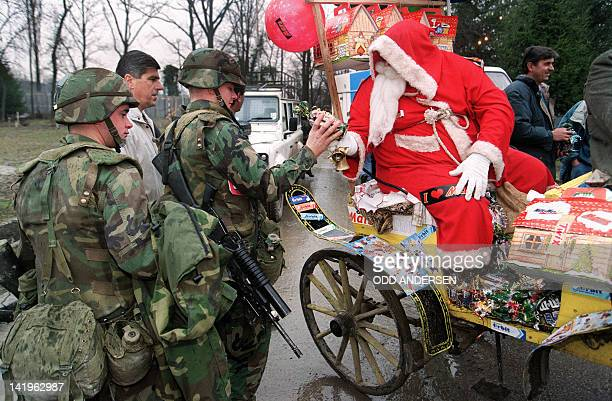 US NATO troopers receive chocolate and sweets from the Santa Claus who pays a visit to Tuzla airbase on December 25 1995 The base is the home and...